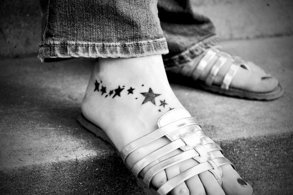 black and white photo of woman's tattooed feet with stars in sandals