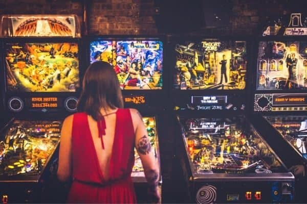 girl red dress playing pinball machines