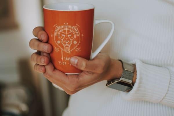 woman holding ceramic mug with leo zodiac sign