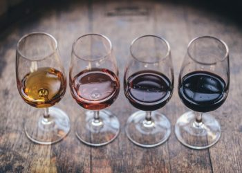 four wines in glasses and barrel
