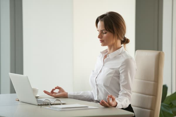 Woman practicing meditation at work